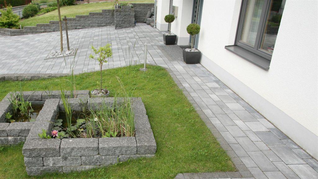 haus umrandung mit pflastersteinen und zufahrt auch mit steinen in farbe grau anthrazit