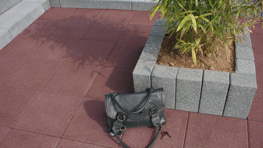 terrassenplatten beton in farbe rot darauf steht eine handtasche aus leder