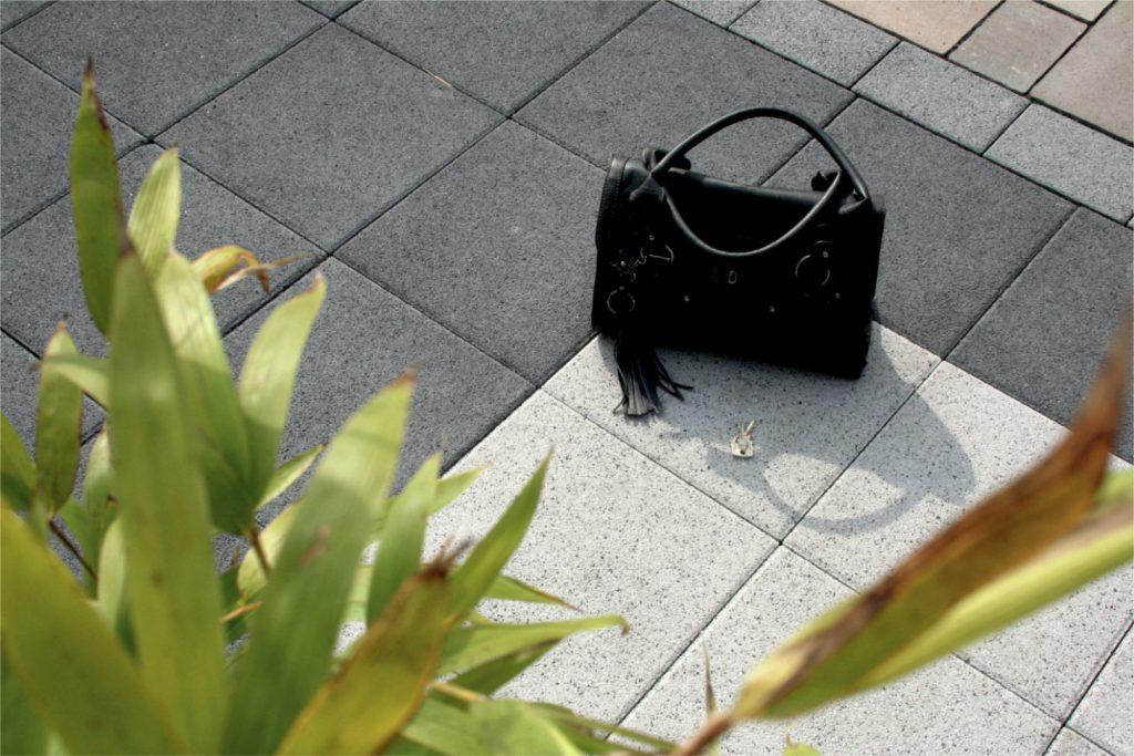 im garten steht eine tasche auf betonplatten
