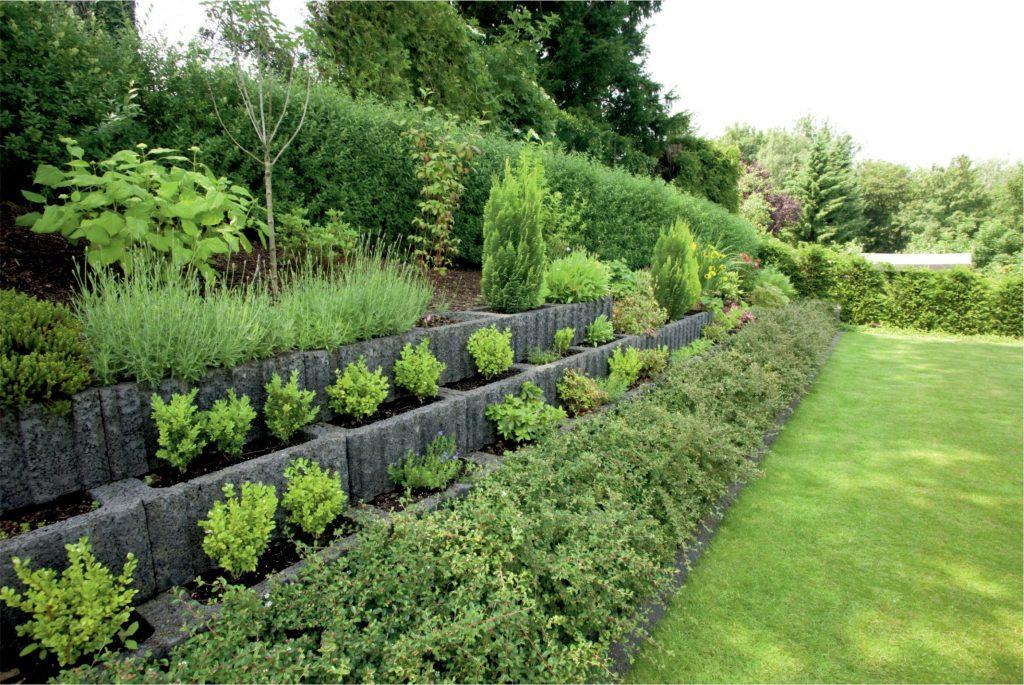 böschungsstein in grau mit pflanzen befüllt