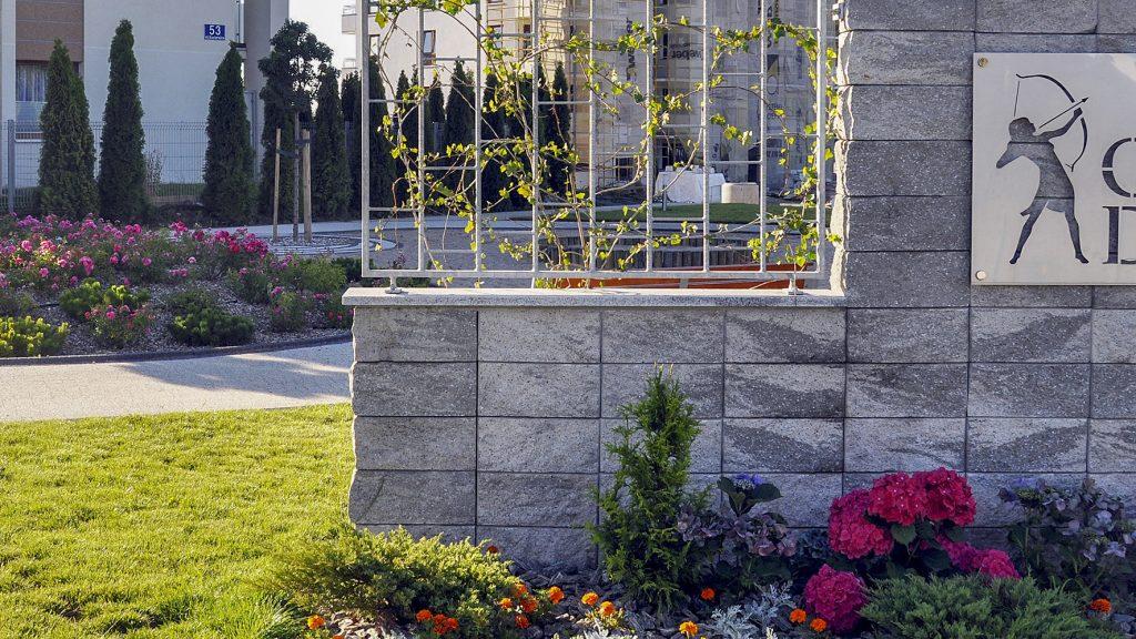 gartenmauer beton mit grando steinen und dahinter sind pflanzen und blumen