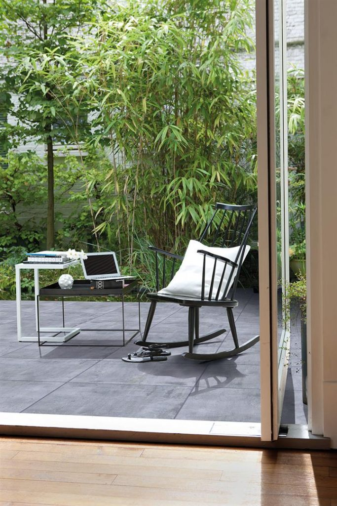 Terrasse mit Liegestuhl und eine Tisch darauf ein Laptop