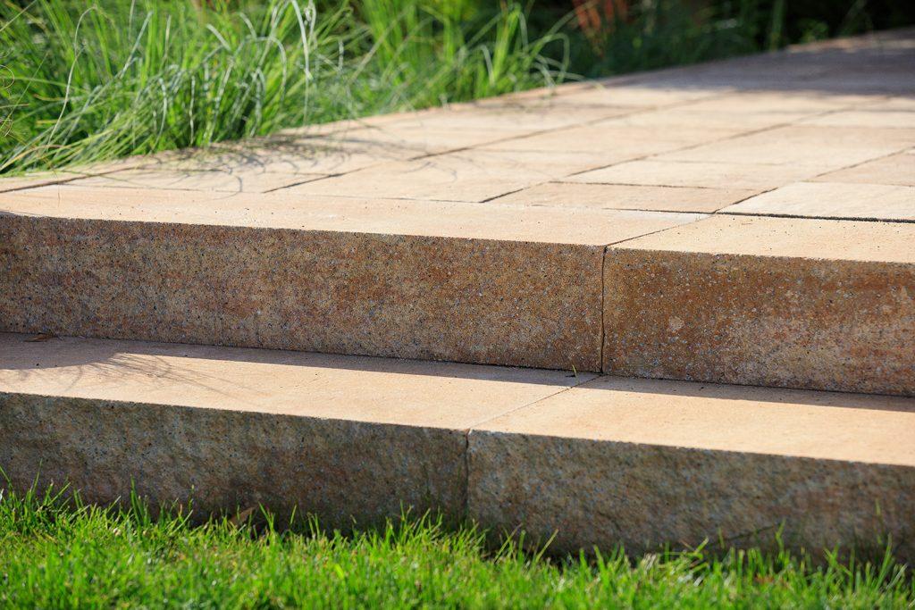 betonstufe detail aufnahme mit gras daneben