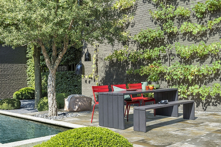 neben einen pool eine gartenbank und tisch