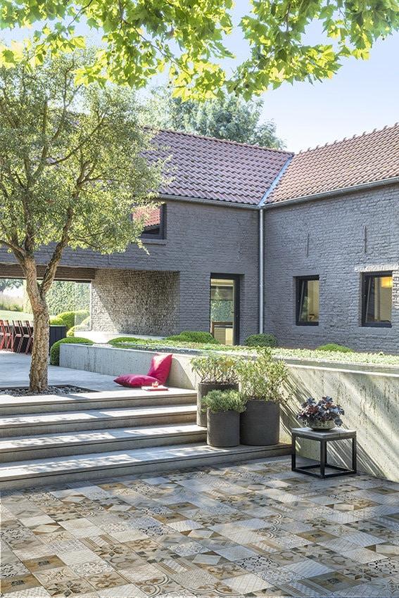Terrassenplatten im Garten und dahinter ein Haus