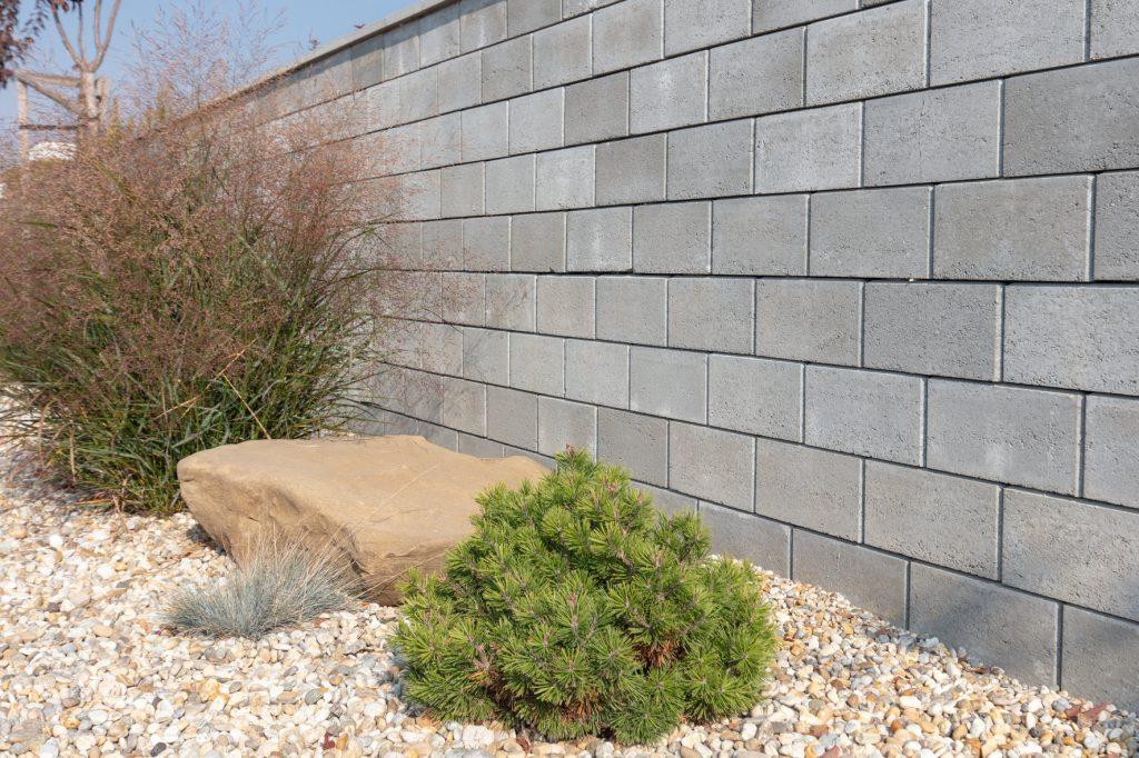 hohlsteine für gartenmauer mit pflanzen und schotter