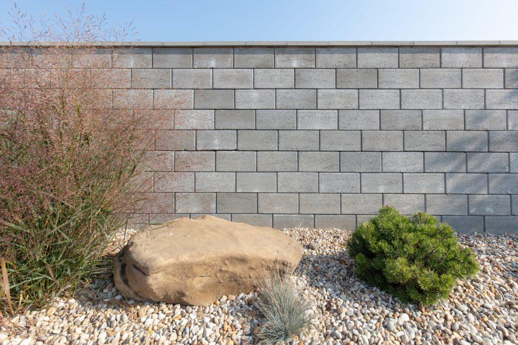 gartenmauer in farbe grau davor schotter und ein strauch