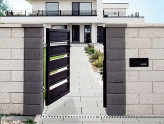 ein gartenzaun aus betonsteinen mit einem tor in der mitte